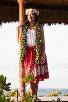 Young Hawaiian woman in hula attire in a beachfront gazebo at sunset