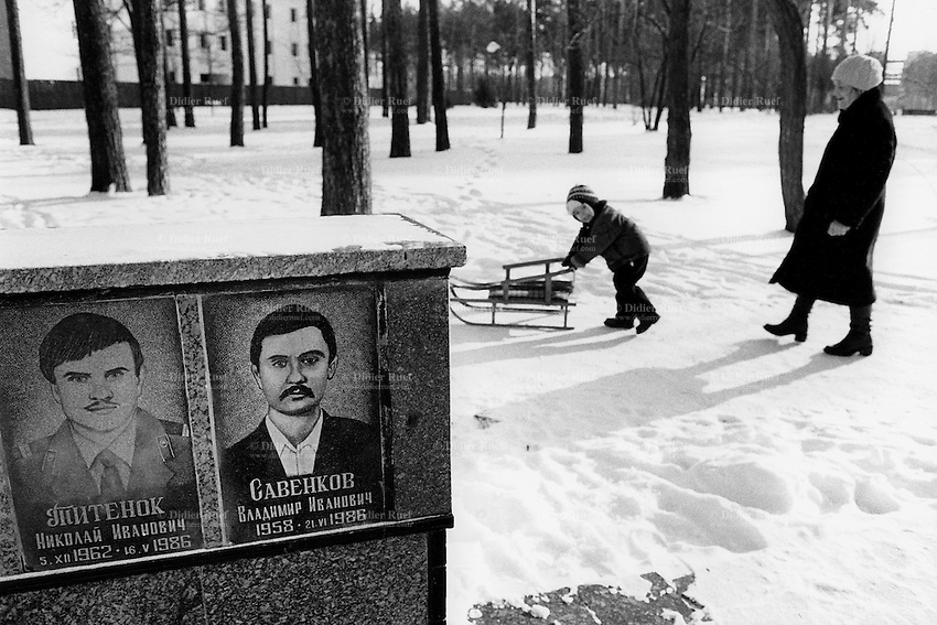 Ukraine. Province of Kiev. Slavutich. A grandmother and her grandson with a sledge walks on a snowy path near the memorial monument for the dead workers of the Chernobyl acident. The town of Slavutich was created after the catastrophe which took place on april 1986 at 1.23 am with the explosion of reactor No 4 at Chernobyl atomic power station. Slavutich is distant 60 km from the power station and was newly built after the evacuation of the inhabitants from both towns of Pripyat and Chernobyl. © 2006 Didier Ruef