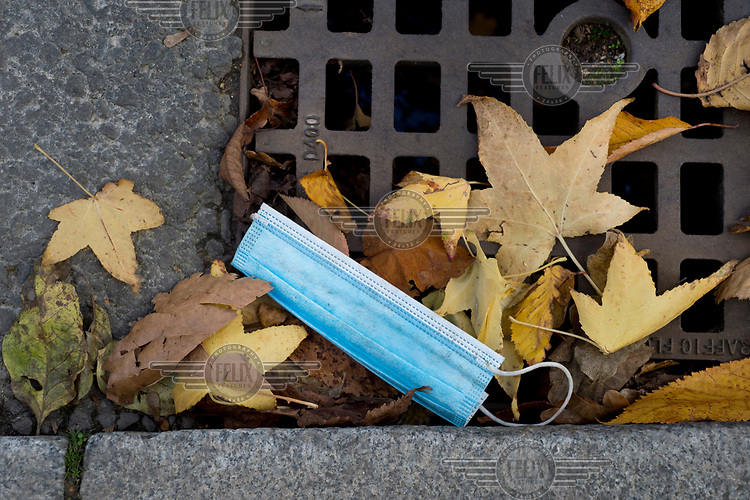 A discarded face mask lies among autumn leaves on a drain on Chatsworth Road, LB Hackney.