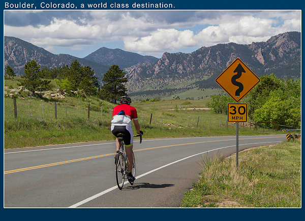 Stage Technique for a Sense of Place.<br /> It's easy to take a photo of cyclist riding by, but I like to give my travel images a sense of place. Dynamic diagonal lines start from the corner and lead into the image. The perfectly placed cyclist is colorful, without any distracting logos. The highway sign is informative and acts as a frame.<br /> Boulder, Colorado, USA.