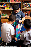 Education preschool 4 year olds group of three boys building together with magnet tiles