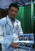 Surgeon Dr Xie Wei-Guo shows a book with before and after pictures of his patients, Shenzhen, China. As the Chinese population grows richer more and people are turning to cosmetic surgeons for nose, eye and breast jobs...PHOTO BY SINOPIX