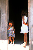 Mato Grosso, Brazil. Two young Rikbaktsa (Canoeiro) Indian sisters at the door of their timber house.
