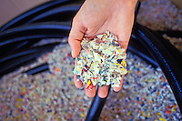 A hand scoops out some shredded plastic from a recycling bin.