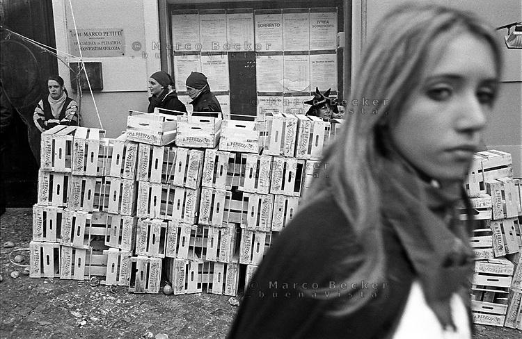 Storico Carnevale di Ivrea, Battaglia delle Arance. Ragazza e barricata di cassette --- Historic Carnival of Ivrea, Battle of the Oranges. Girl and barricade of boxes
