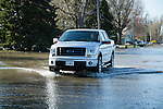 Woman driving car in flooded street