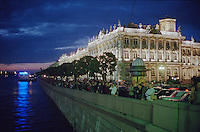 Saint Petersburg, Russia, June 2002..The mid-summer White Nights period when the sun sets only briefly is a time of festivals, entertainment and walks along the Neva River to watch the city bridges raise for shipping. Crowds gather nightly by the Hermitage to watch Palace Bridge raise at 2 am for the night shipping during the White Nights..