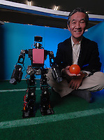 Ken Tomiyama head of Advanced Robotics at the Chiba Institute of Technology with some of his football playing robots..