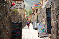 In the town of Ollantaytambo, a Peruvian women walks down a narrow road surrounded by stonewalls. This road is predominantly empty, but has many pizzerias, restaurants, and shops for the locals to stop in on their way to and from work.