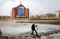 China. Jilin Province. A woman crosses a river in the town of Yanji, close to the border with North Korea. The town is part of the Korean Autonomous Prefecture in the north-east of the country. Christianity is prevalent in the region and churches can be seen in major towns. 2011