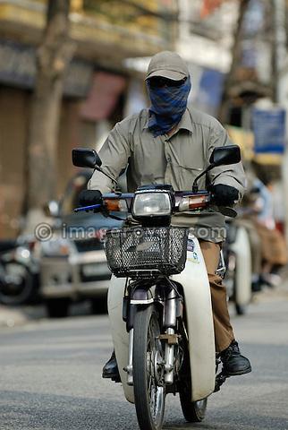 Asia, Vietnam, Hanoi. Hanoi old quarter. Vietnamese men riding on a motorbike (moped) through Hanoi.