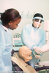 Female teenager in dentisry school to work program learning skills before high school graduation shown techniques by more experienced technician, using manikin of human head