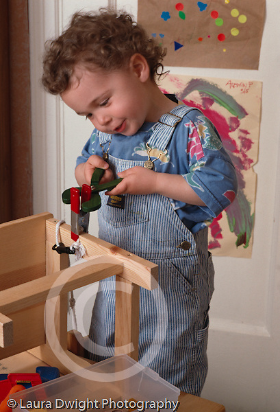 2 year old toddler boy pretend play construction carpentry using toy tool pliers on chair leg vertical Caucasian