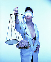 Busty blindfolded woman in lab coat holding scales weighing brain<br />