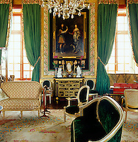 A portrait of Louis XVI's brother and his wife look down on the formal drawing room with its stunning colour scheme of of vivid green, gold and black