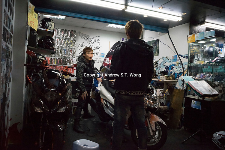 """Taiwanese youths check out a motorbike at a workshop in Ximending District, Taipei, Taiwan, 2015. Ximending has been a famous area for shopping and entertainment since the 1930s. Historic structures include a concert hall, a historic cinema, and the Red House Theatre. Modern structures house karaoke businesses, art film cinemas, wide-release movie cinemas, electronic stores, and a wide variety of restaurants and fashion clothing stores. The pedestrian area is especially popular with teens and has been called the """"Harajuku"""" of Taipei."""