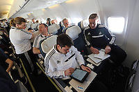 Wednesday 26 February 2014<br /> Pictured: Head coach Garry Monk (R) with assistant Pep (C) on the aeroplane en route to Napoli.<br /> Re: Swansea City FC travel to Italy for their UEFA Europa League game against Napoli.
