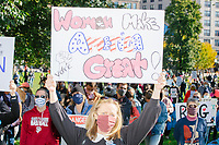 """A crowd gathers in Boston Common for the 2020 Women's March protest in opposition to the re-election of US president Donald Trump in Boston, Massachusetts, on Sat., Oct. 17, 2020.<br /> The sign here reads """"Women make America great!"""""""