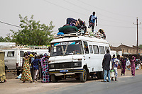Senegal, Touba.  Local Transport and Traffic Safety.  Young Men load goods on top; some passengers will ride there.