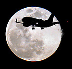 Airliner jet is silhouetted by March's super moon at SFO.