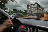 """Nigeria. Enugu State. Traffic on the road to Awhun. Cars and trucks on dirt road. Hand on steering whell. A truck driven by a muslim Hausa man has a drawing on the back of his lorry. The sketch is about a moslem man kneeling on a carpet and doing one of his five daily prayers, and on the side a tea-pot. Salah (also called salat), is one of the Five Pillars in the Islamic faith, and an obligatory religious duty for every Muslim. It is a physical, mental, and spiritual act of worship that is observed five times every day at prescribed times. When they do this, they must face to Mecca, towards the Qiblah. In this ritual, one stands, bows, and prostrates oneself, and concludes sitting on the ground. During each posture, one recites or reads certain verses, phrases, and prayers. On the bottom, the words from the inaugural speech by His Excellency, President Muhammadu Buhari following his swearing-in as President of the Federal Republic of Nigeria on 29th May, 2015:  """"I belong to everybody & I belong to nobody"""". Muhammadu Buhari (born 17 December 1942) is a Nigerian politician currently serving as the President of Nigeria, in office since 2015. He is a retired major general in the Nigerian Army and previously served as the nation's head of state from 31 December 1983 to 27 August 1985, after taking power in a military coup d'état. 29.06.19 © 2019 Didier Ruef"""