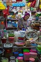 Yogyakarta, Java, Indonesia.  Woman Selling Home Utensils and Sundry Items, Beringharjo Market.