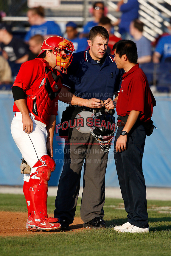 August 5, 2009:  Home plate umpire Tim Rosso gets some assistance for a broken helmet from Muckdogs catcher Alan Ahmady and Trainer Manabu Kuwazuru during a game at Dwyer Stadium in Batavia, NY.  Photo By Mike Janes/Four Seam Images