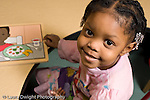 Educaton preschool  3-4 year olds closeup portrait of happy girl smiling wooden puzzle on table horizontal
