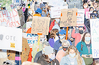 """A crowd gathers in Boston Common for the 2020 Women's March protest in opposition to the re-election of US president Donald Trump in Boston, Massachusetts, on Sat., Oct. 17, 2020.<br /> The signs here read """"Fight like a girl"""" (featuring an image of Supreme Court Justice Ruth Bader Ginsburg), """"Make Margaret Atwood Fiction Again,"""" """"This is how it starts,"""" """"Vote,"""" and """"RBG Legacy / Rest in Power."""""""