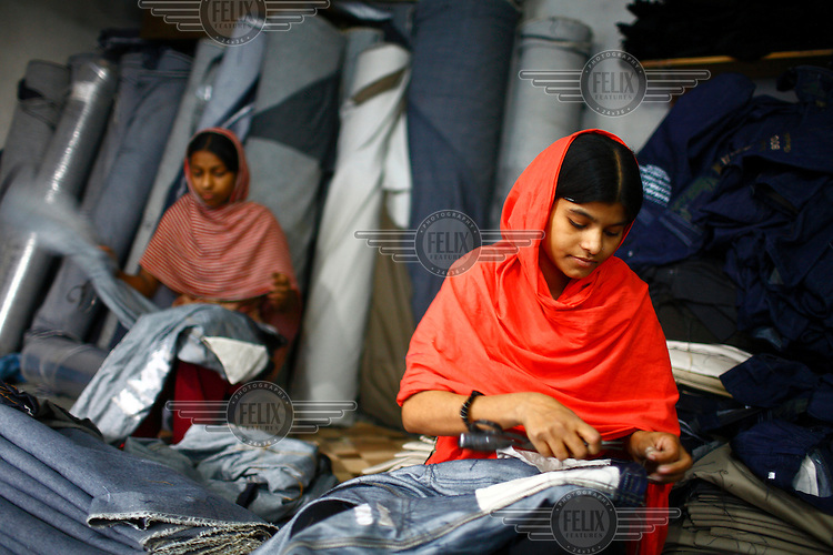 Women working in a small garment factory trim threads on a newly made pair of denim jeans.