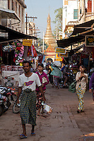 Myanmar, Burma. Mandalay Market Street, Ein Daw Yar Pagoda in distance.  Man is wearing a longyi, the traditional sarong-like wrap-around garment.