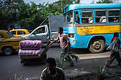 Workers push a trolley while vehicles wait for traffic light to turn green in Kolkata, West Bengal, India.