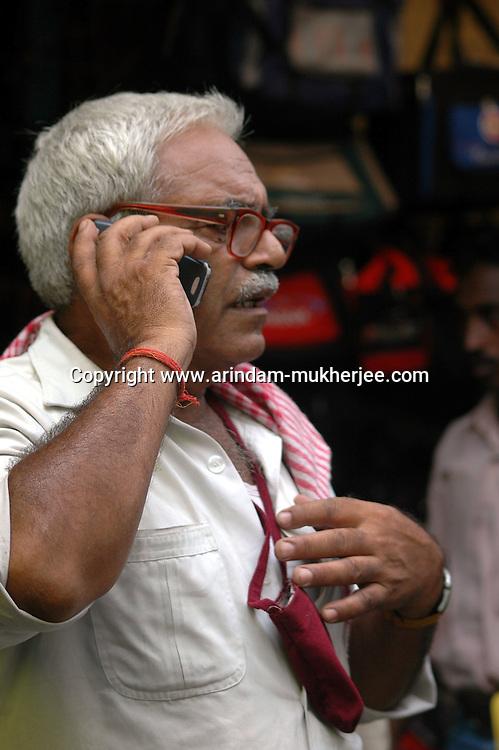 An old Indian man using a mobile phone on a road of  Kolkata, West Bengal,  India  7/18/2007.  Arindam Mukherjee/Landov