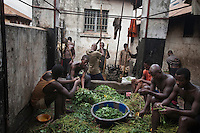 Prisoners in Pademba Central Prison pound potato and cassava leaves, which along with rice is the staple food. They recieve tea and a piece of bread in the morning but meat and fish are only available to the few inmates who have the money to pay for it..