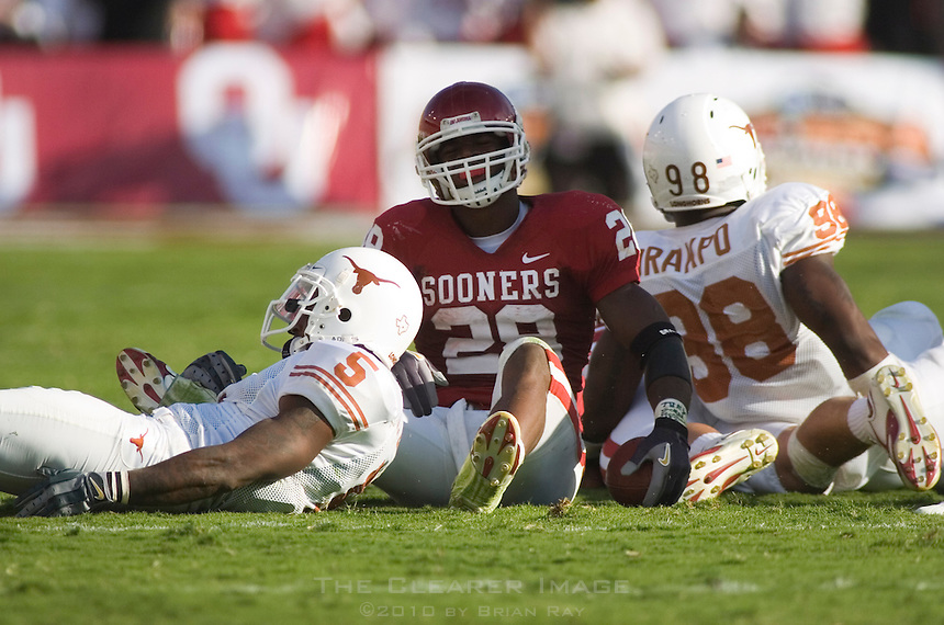 07 October 2006: Oklahoma back Adrian Peterson (#28) sits on the ground after being tackled by Texas defenders Tarell Brown (#5) and Brian Orakpo (#98) during the Sooners 28-10 loss to the University of Texas Longhorns at the Cotton Bowl in Dallas, TX.