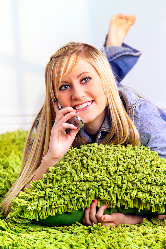 Blonde teenage girl communicating on cell phone.