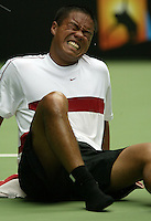 Qualifier Cecil Mamiit grimaces in pain after he ran into a line umpire's chair and injured his foot, forcing him to forfeit this  first round match against Lleyton Hewitt at the Australian Open. - pic by Trevor Collens