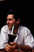 Rio Grande do Sul, Brazil.  Man holding a chimarrao with mate tea looking into the distance.