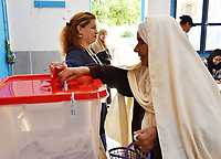 A Tunisian voter casts her ballot at a polling station in the capital Tunis on October 13, 2019 during the second round of the presidential election. - Tunisians began voting today in a presidential runoff pitting conservative law professor Kais Saied against media magnate Nabil Karoui, who was released from prison just days earlier.