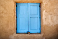 Window with rock closure and adobe wall. Taos, NM