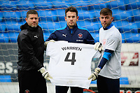 Blackpool's goalkeeper coach Steve Banks, left, Blackpool's Chris Maxwell, centre, and Blackpool's Jack Sims with a t-shirt in tribute to Warren Green, Blackpool's academy manager, who died aged 46<br /> <br /> Photographer Chris Vaughan/CameraSport<br /> <br /> The EFL Sky Bet League One - Peterborough United v Blackpool - Saturday 21st November 2020 - London Road Stadium - Peterborough<br /> <br /> World Copyright © 2020 CameraSport. All rights reserved. 43 Linden Ave. Countesthorpe. Leicester. England. LE8 5PG - Tel: +44 (0) 116 277 4147 - admin@camerasport.com - www.camerasport.com