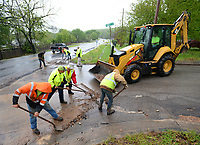City of Fayetteville Transportation Division employees remove debris Wednesday, April 28, 2021, from the intersection of Kings Drive and Mission Boulevard after heavy rains washed spoils from road milling work down Kings Drive which is being prepared for resurfacing. Crews responded to several calls to clear streets that had become covered with water during the day's storms. Visit nwaonline.com/210429Daily/ for today's photo gallery. <br /> (NWA Democrat-Gazette/Andy Shupe)
