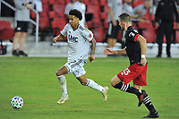 WASHINGTON, DC - SEPTEMBER 27: Tajon Buchanan #17 of New England Revolution battles for the ball with Frederic Brilliant #13 of D.C. United during a game between New England Revolution and D.C. United at Audi Field on September 27, 2020 in Washington, DC.