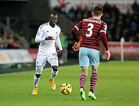 Pictured L-R: Modou Barrow of Swansea against Aaron Cresswell of West Ham Saturday 10 January 2015<br /> Re: Barclays Premier League, Swansea City FC v West Ham United at the Liberty Stadium, south Wales, UK