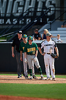Siena Saints Devan Kruzinski (12) and first base coach Anthony Spataro look for the sign in between umpire Rick Darby and first baseman Dallas Beaver (38) during a game against the UCF Knights on February 17, 2019 at John Euliano Park in Orlando, Florida.  UCF defeated Siena 7-1.  (Mike Janes/Four Seam Images)