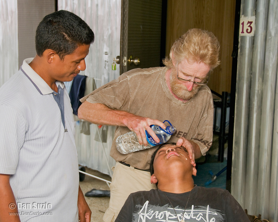 British herpetologist Mark O'Shea and Timorese student Benny Carvalho attend to American student Jester Ceballos, who had accidentally gotten Formalin in his eye while preparing specimens at a makeshift research station at Bakhita Mission, Near Eraulo, Ermera District, Timor-Leste (East Timor)