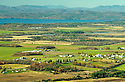 Farm and field leads to Lake Champlain and the Adirondack Mountains beyond in this almost-arial photograph of Addison, Vermont.