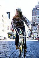 Woman on banana seat bicycle in middle of street<br />