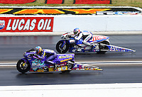 Sept. 2, 2013; Clermont, IN, USA: NHRA pro stock motorcycle rider L.E. Tonglet (near lane) races alongside Hector Arana Jr during the US Nationals at Lucas Oil Raceway. Mandatory Credit: Mark J. Rebilas-