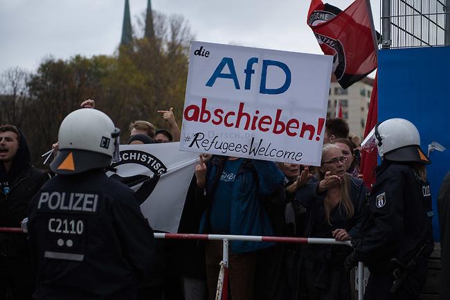 """Bis zu 2500 Anhaenger der Rechtspartei """"Alternative fuer Deutschland"""" (AfD) versammelten sich am Samstag den 7. November 2015 in Berlin zu einer Demonstration. Sie protestierten gegen die Fluechtlingspolitik der Bundesregierung und forderten """"Merkel muss weg"""". Die Demonstration sollte der Abschluss einer sog. """"Herbstoffensive"""" sein, zu der urspruenglich 10.000 Teilnehmer angekuendigt waren.<br /> Mehrere tausend Menschen protestierten gegen den Aufmarsch der Rechten und versuchten an verschiedenen Stellen die Route zu blockieren. Gruppen von AfD-Anhaengern wurden von der Polizei durch Einsatz von Pfefferspray, Schlaege und Tritte durch Gegendemonstranten, die sich an zugewiesenen Plaetzen aufhielten, zur rechten Demonstration gebracht. Zum Teil wurden sie von Neonazis-Hooligans dabei angefeuert. Dabei kam es zu Verletzten, mehrere Gegendemonstranten wurden festgenommen.<br /> Im Bild: AfD-Gegner protestieren am Rande des AfD-Aufmarsches.<br /> 7.11.2015, Berlin<br /> Copyright: Christian-Ditsch.de<br /> [Inhaltsveraendernde Manipulation des Fotos nur nach ausdruecklicher Genehmigung des Fotografen. Vereinbarungen ueber Abtretung von Persoenlichkeitsrechten/Model Release der abgebildeten Person/Personen liegen nicht vor. NO MODEL RELEASE! Nur fuer Redaktionelle Zwecke. Don't publish without copyright Christian-Ditsch.de, Veroeffentlichung nur mit Fotografennennung, sowie gegen Honorar, MwSt. und Beleg. Konto: I N G - D i B a, IBAN DE58500105175400192269, BIC INGDDEFFXXX, Kontakt: post@christian-ditsch.de<br /> Bei der Bearbeitung der Dateiinformationen darf die Urheberkennzeichnung in den EXIF- und  IPTC-Daten nicht entfernt werden, diese sind in digitalen Medien nach §95c UrhG rechtlich geschuetzt. Der Urhebervermerk wird gemaess §13 UrhG verlangt.]"""